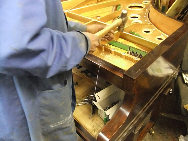 Inserting tuning pins grand piano - detail
