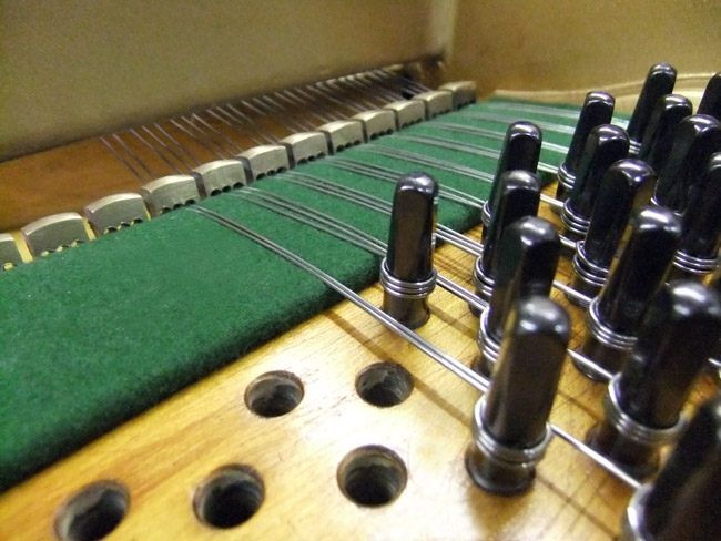Inserting tuning pins and restringing grand piano - detail
